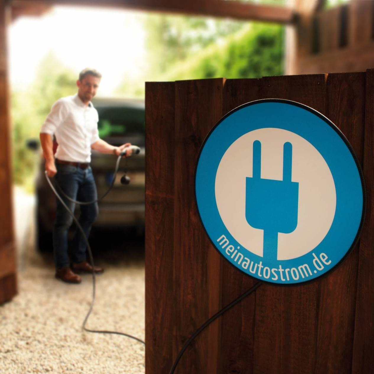 meinAutostrom-Ladebox vor Holzwand, Auto und Mann im Hintergrund