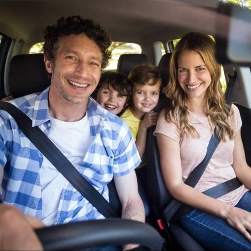 glückliche Familie im Auto, lachenende Kinder und Eltern