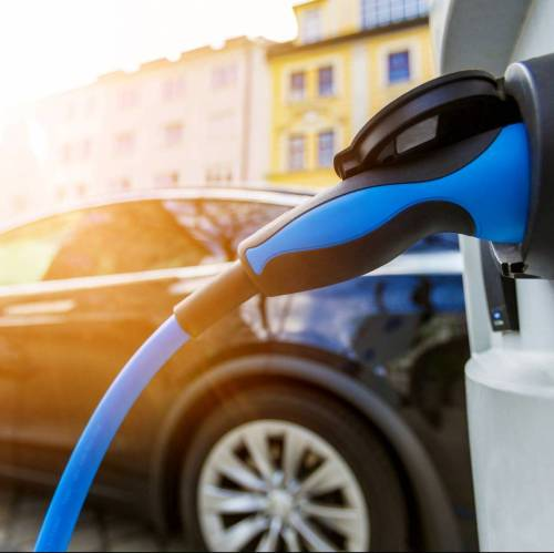 Elektromobilität - blauer Typ 2 Ladestecker vor dunklem Auto