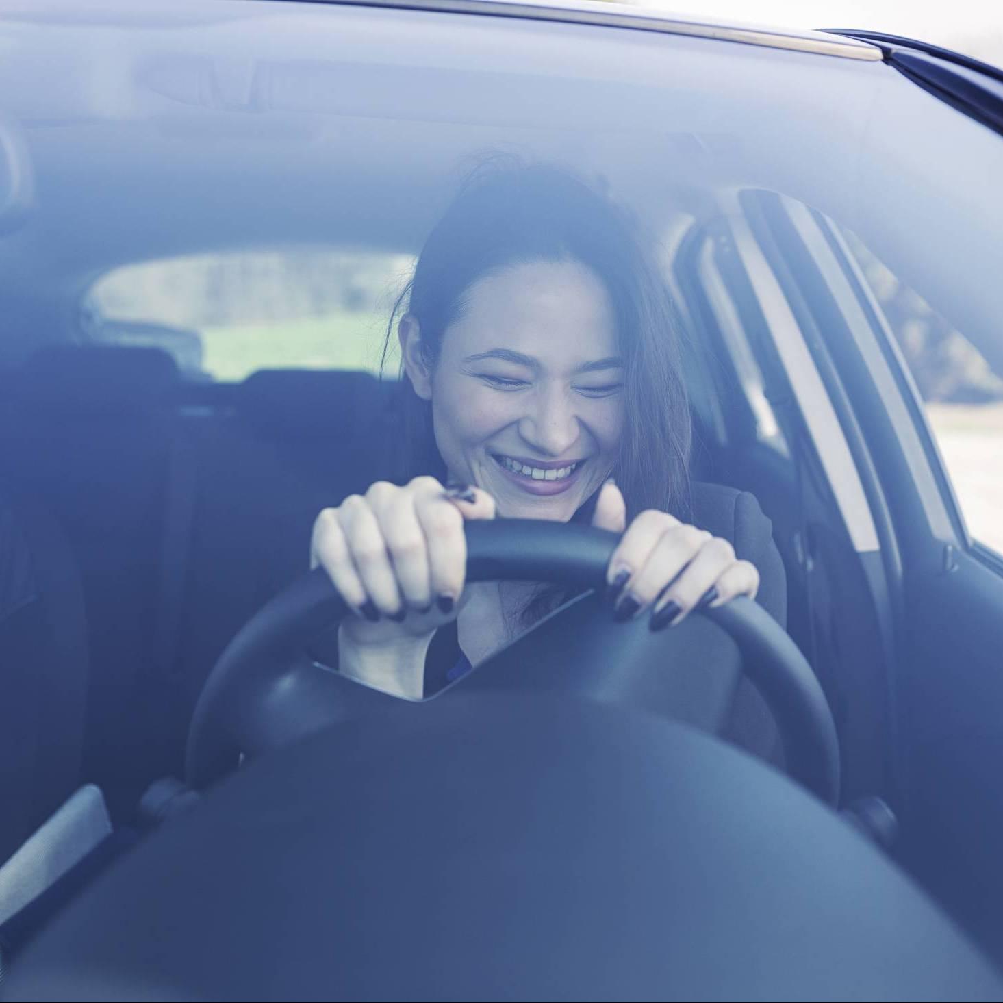 lachende Frau am Steuer eines E-Autos, Emotionen, Freude